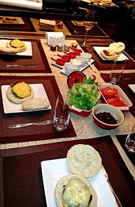 Mesa com tudo que precisa para comer hambúrguer caseiro. Tomate, alface, maionese, catchup, queijos gruyere, prato, camembert e roquefort.